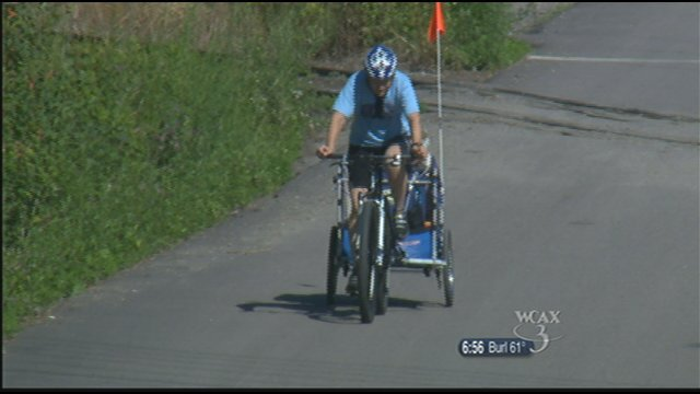 Diana Hanks pulls her dog Gunner up a hill in a cart attached to her bike.