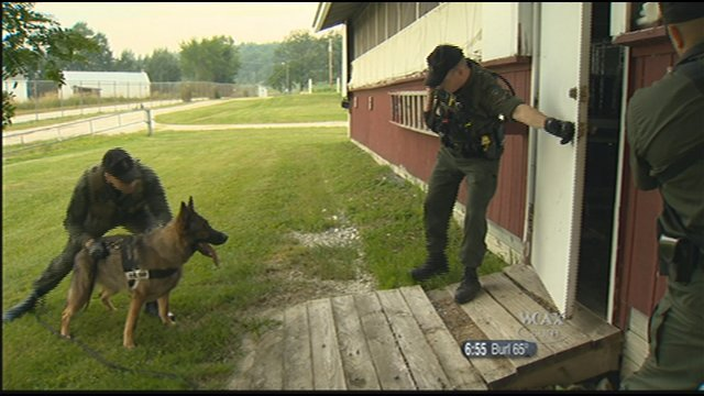 Trooper Bob Giolito and K-9 Mitch apprehend a suspect inside a barn.